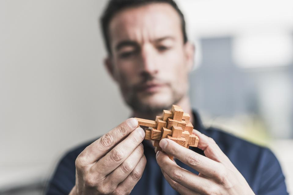 Mature man sitting in office assembling wooden cube puzzle