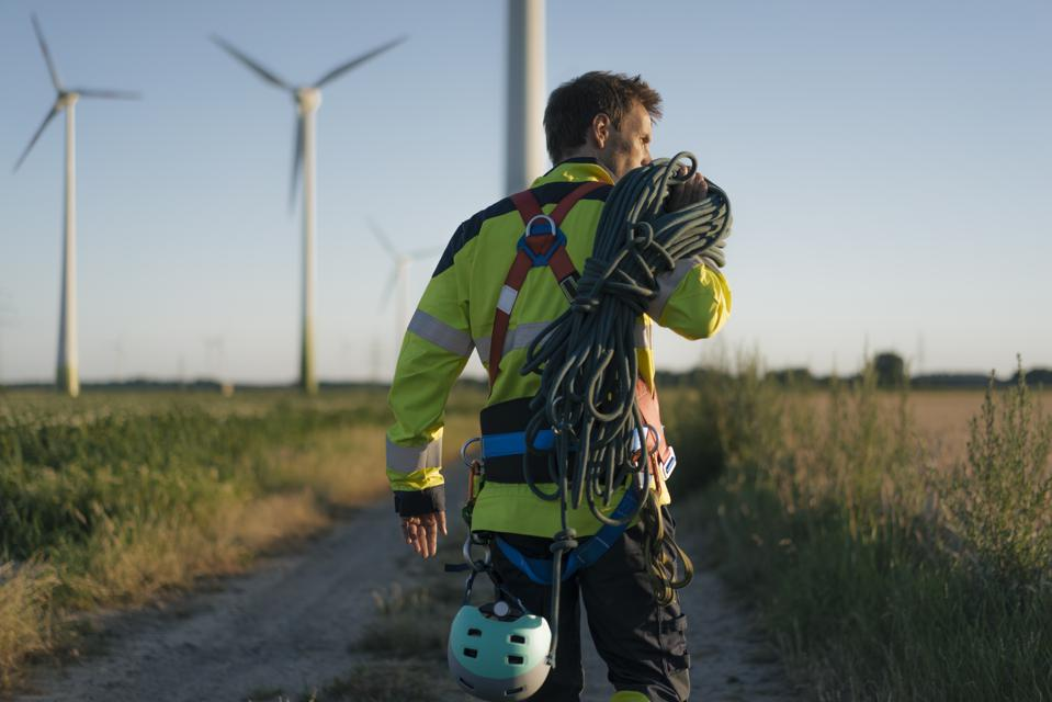 Technician walking on field path at a wind farm with climbing equipment