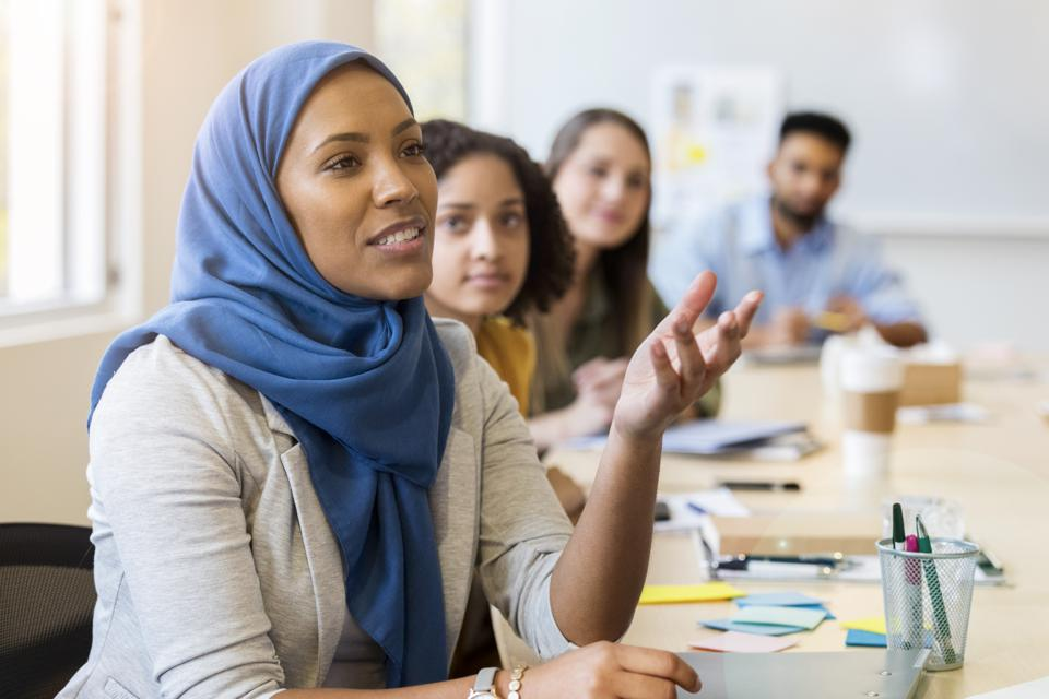 Young Muslim woman speaks to coworkers during staff meeting
