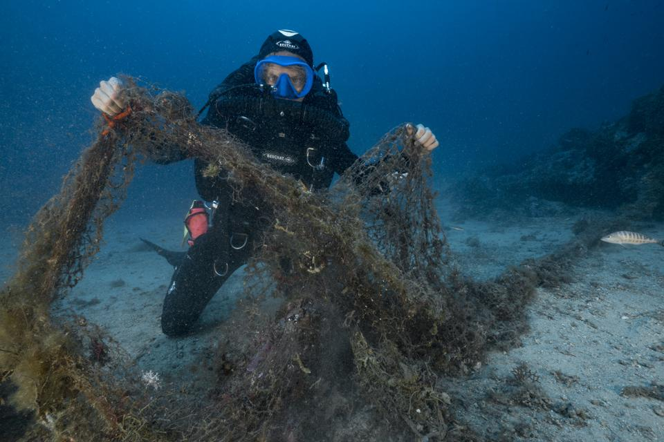 Scuba diver with ghost net.