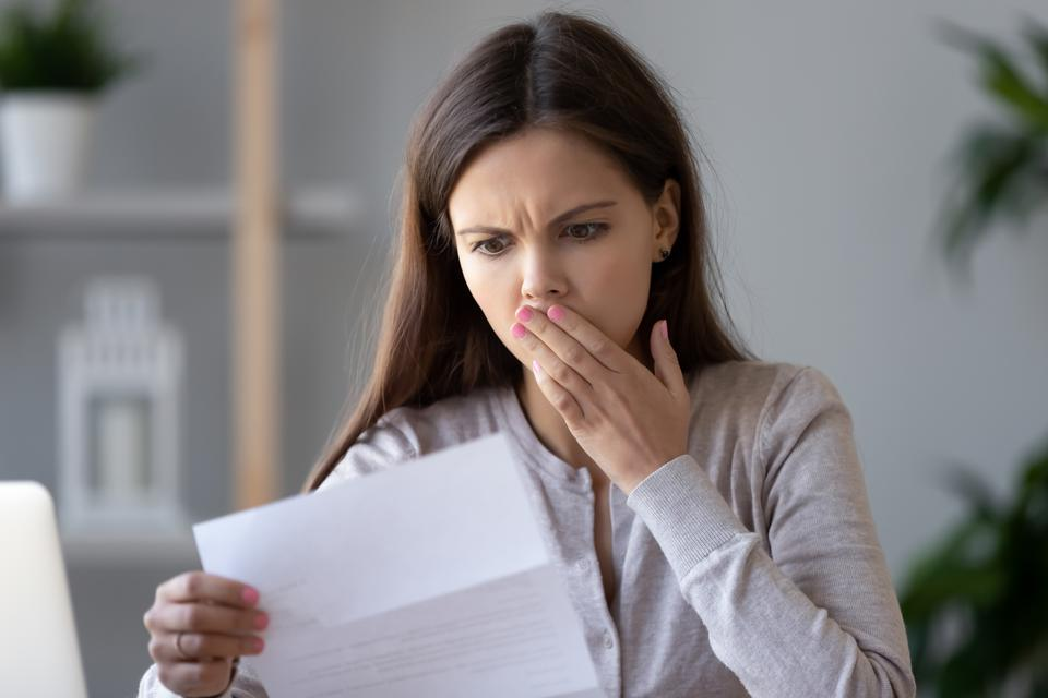 Shocked stressed young woman reading document letter about debt