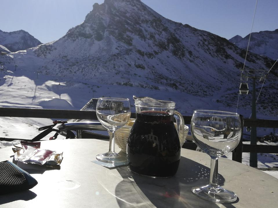 Wine jug with two glasses on the ski slopes on a sunny day