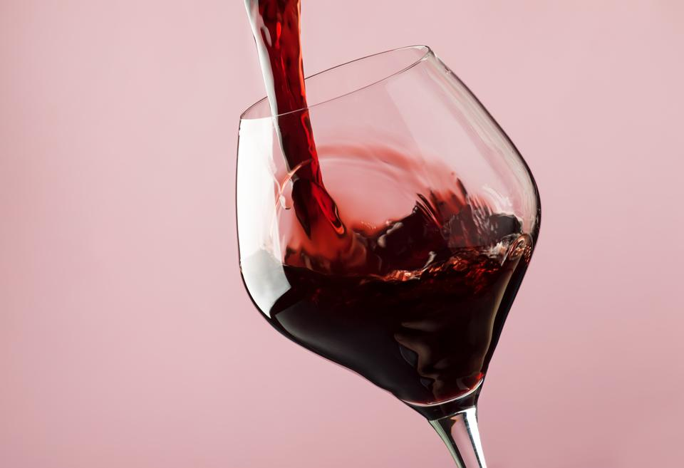 French dry red wine, pours into glass, trendy pink background