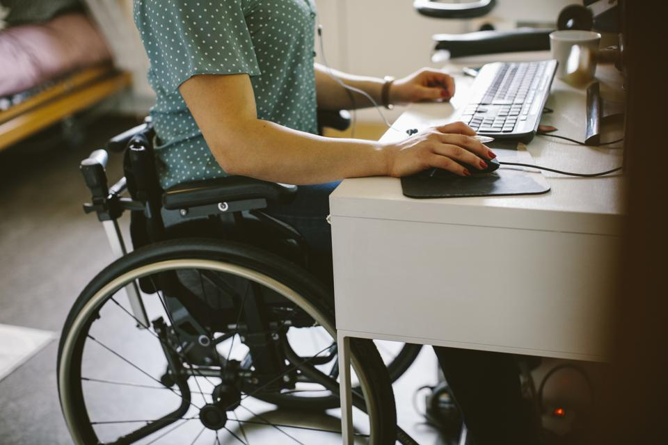 Midsection of young disabled woman using computer at home