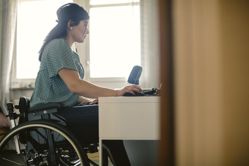 Side view of young disabled freelance worker using computer at desk in room