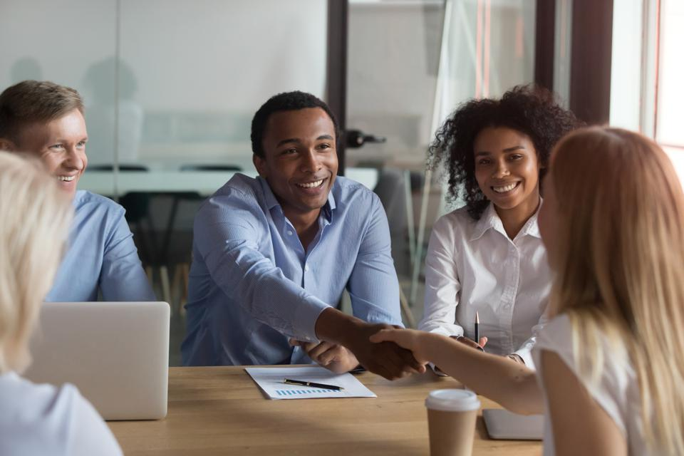 Black ceo handshaking with woman financier while sitting at meeting