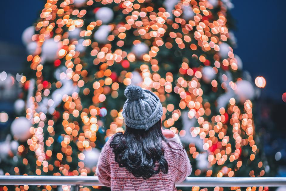 Rear View Of Woman Looking At Illuminated Christmas Lights