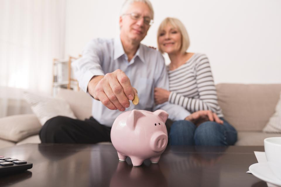 Senior couple saving money in piggybank at home