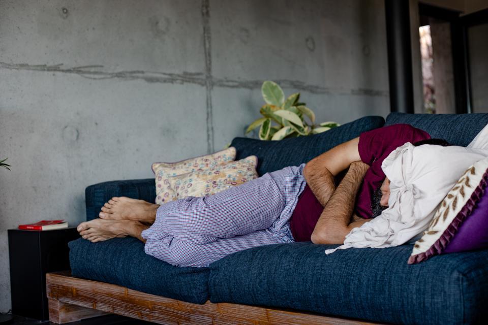 A man lying down on a sofa, sleeping