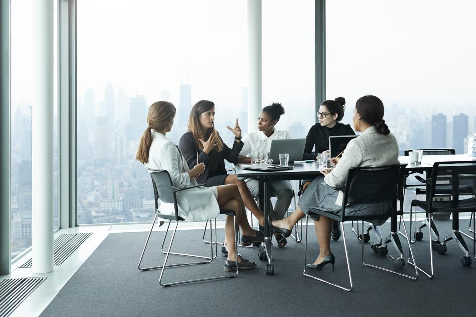 Group of businesswomen having meeting in boardroom with stunning skyline view
