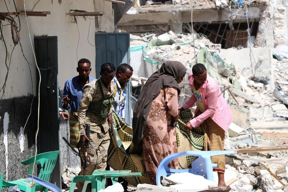 Four men and one woman hold a long fabric containing a body, amidst rubble