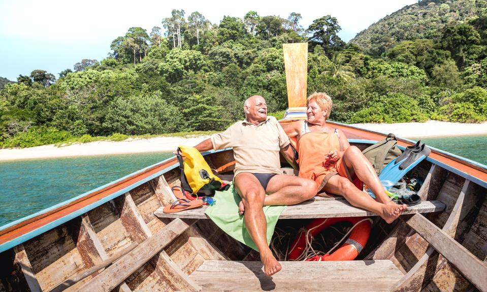 Senior couple vacationer relaxing at island hopping tour after beach exploration during snorkel boat trip in Thailand - Active elderly and travel concept on tour around world - Warm day bright filter