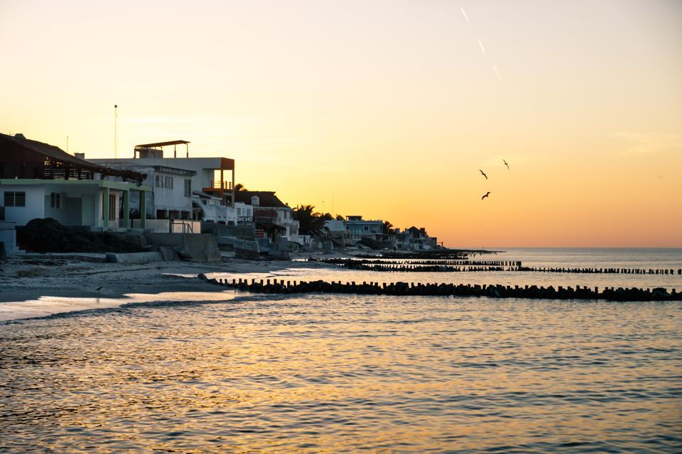 Sunset with orange sky along the coast of Chelem, Mexico