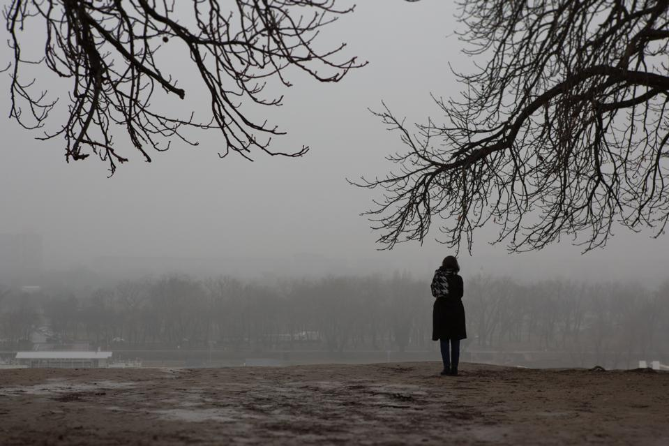 Girl standing alone in the park on gloomy day.