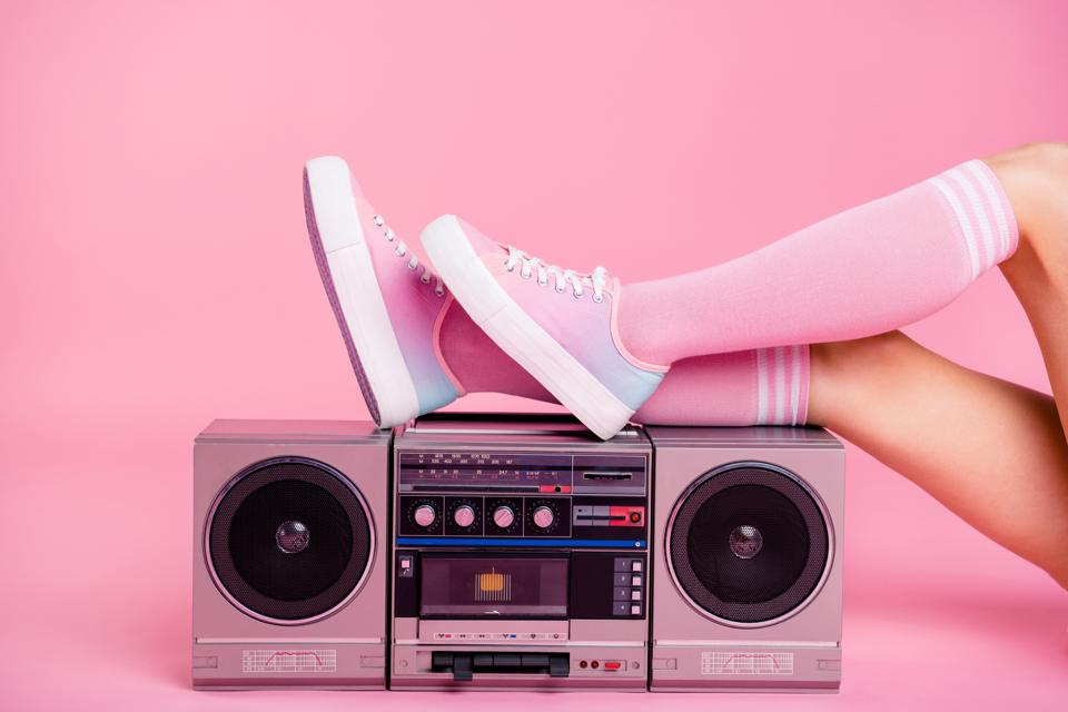 Teen resting legs on boombox