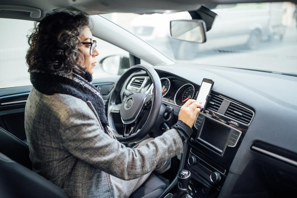 Woman uses navigation on her mobile phone in the car