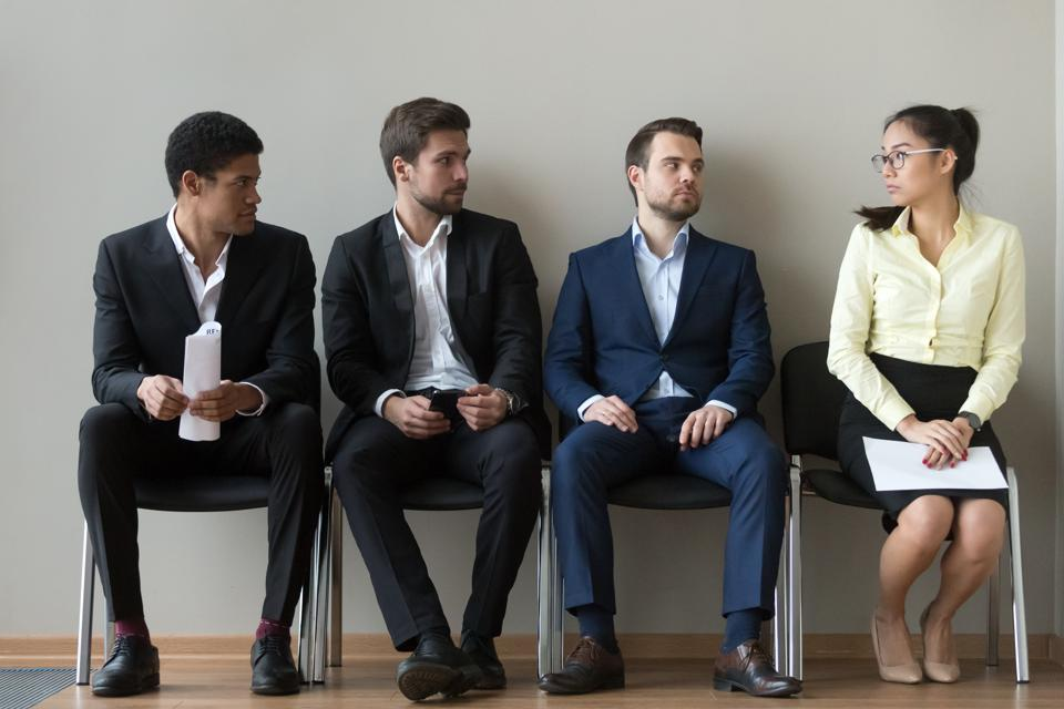 Male applicants looking at female rival waiting for interview