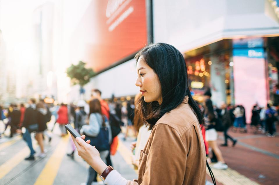 Young woman checking on mobile phone while crossing street and commuting in busy downtown city street