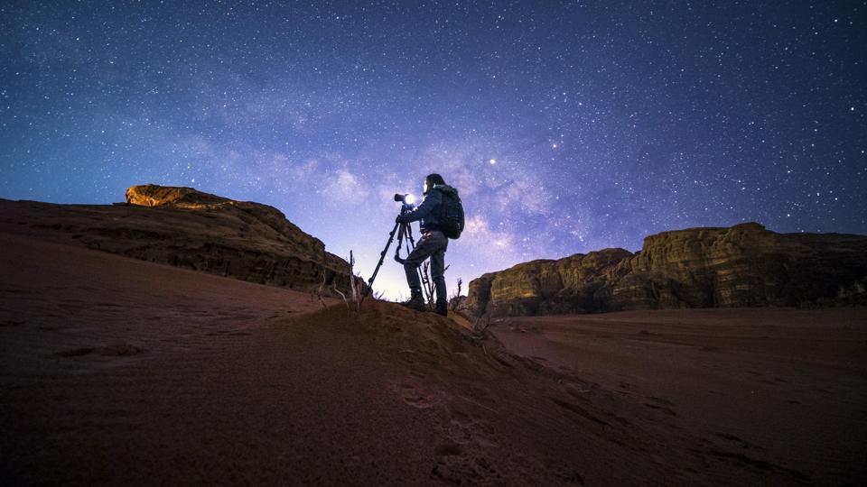 An unidentified photographer in Wadirum desert under the milky way, Jordan