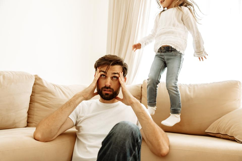 Parenthood. Family. Tired. Dad is having a headache while his little daughter is jumping on the couch at home.