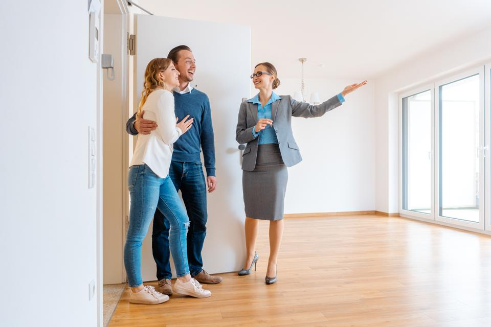 Realtor showing house to a young couple