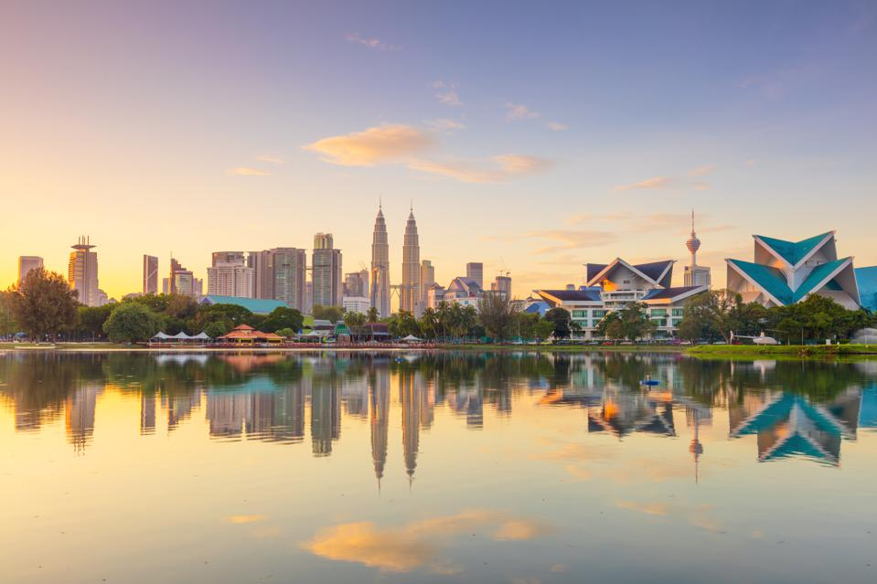 Panoramic view of Kuala Lumpur city waterfront skyline with reflections and beautiful morning sky