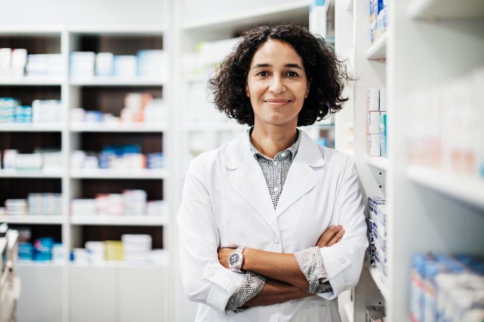 Portrait Of Pharmacist Standing Next To Medical Supplies