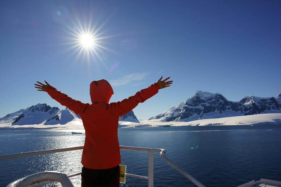 Woman watching the glacier in Antarctica from the boat