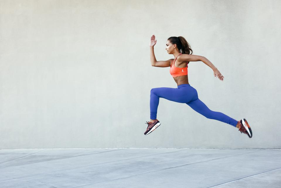 Side view of young woman wearing sports clothing in mid air striding stance