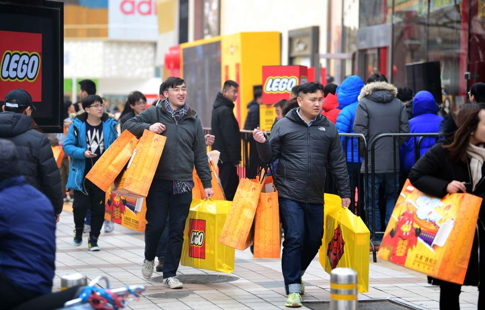Lego Opens Flagship Store In Beijing, Shoppers carrying bright yellow Lego bags