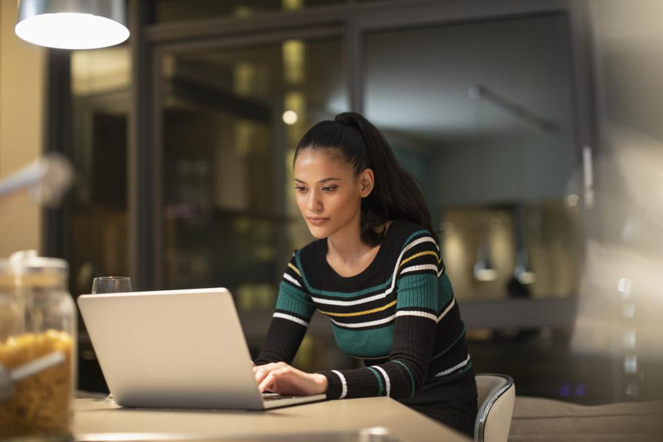 Focused woman using laptop at home at night