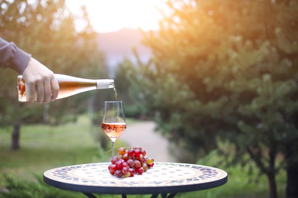 Man pouring rose wine to the glass in autumn vineyard on marble table