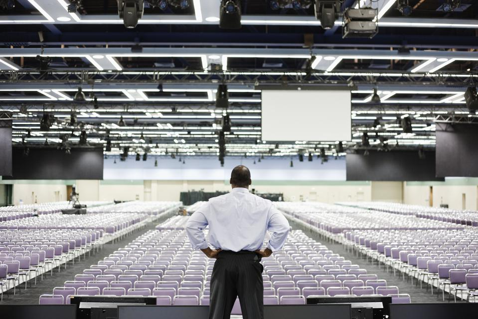 Black businessman standing on stage in empty conference center
