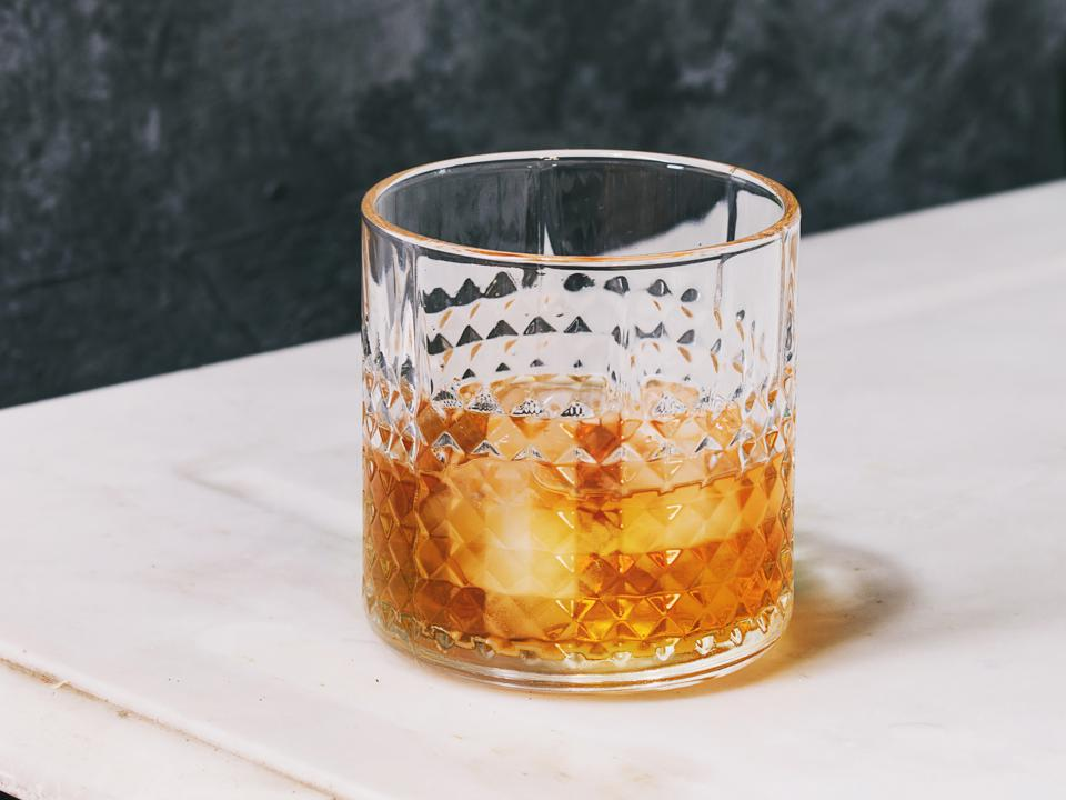 Glass of whiskey on ice standing on white marble table with grey wall at background. Alcohol drink.