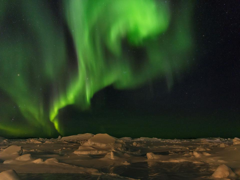 Northern lights over the shore of the frozen Disko Bay.
