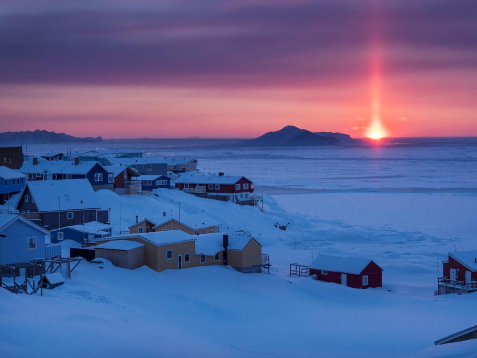 Sunset over icefjord and town. Town Ilulissat at the shore of Disko Bay in West Greenland. center for tourism. administration and economy. The icefjord nearby is listed as UNESCO world heritage. America. North America. Greenland. Denmark