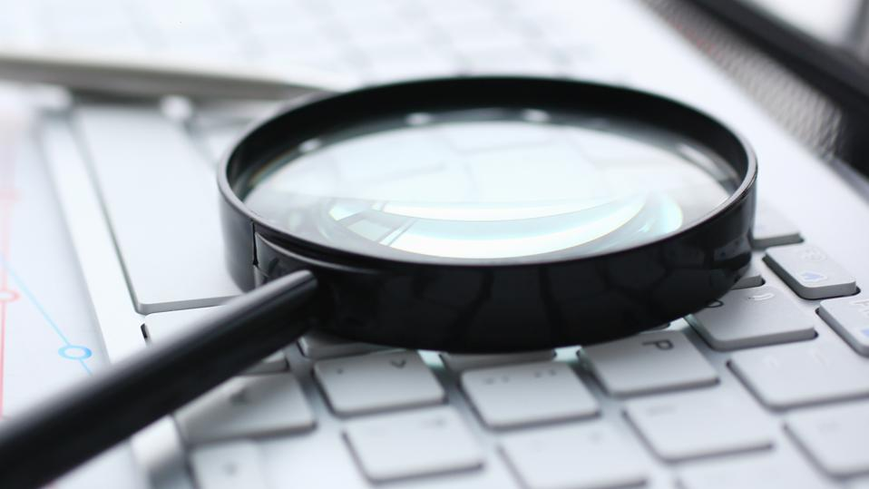 Magnifying glass lies on white keyboard on