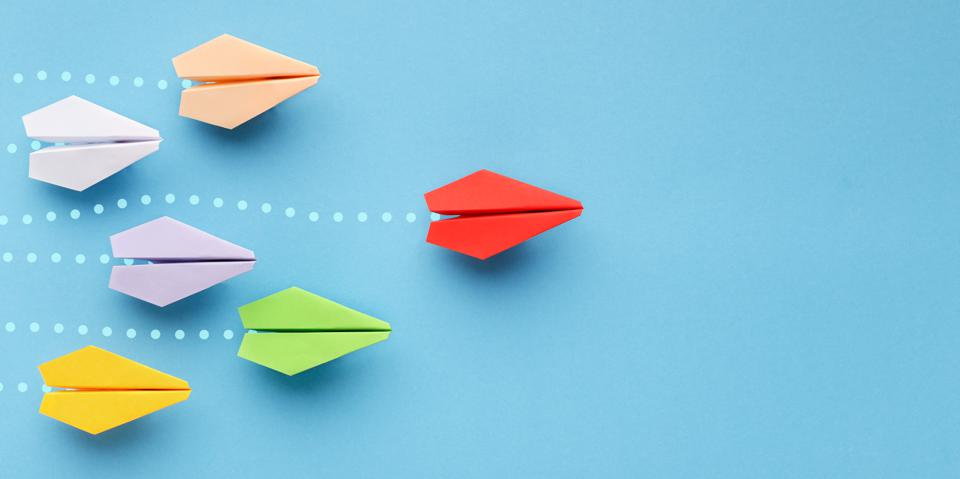Red paper plane leading another colorful ones, influencing the crowd, blue background,