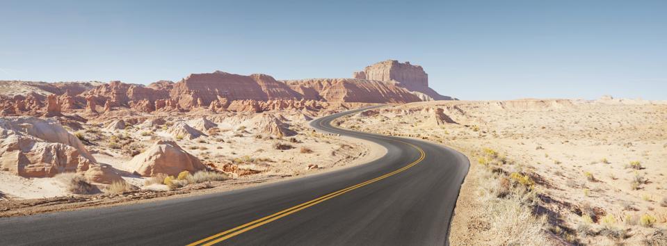 Winding empty road through arid desert landscape panoramic