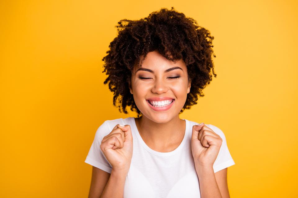 Close up photo beautiful amazing she her dark skin lady hands arms fists raised eyes closed great big win competition wear casual white t-shirt isolated yellow bright vibrant vivid background