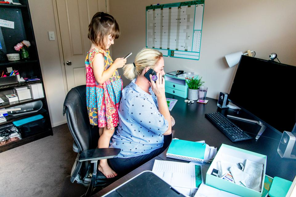 Woman working from home in office whilst also looking after her young daugther.