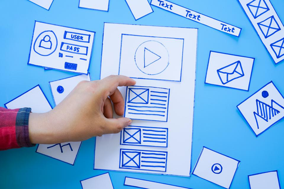 Creative mobile responsive website designer sorting wireframe screens of mobile application process development prototype wireframe.