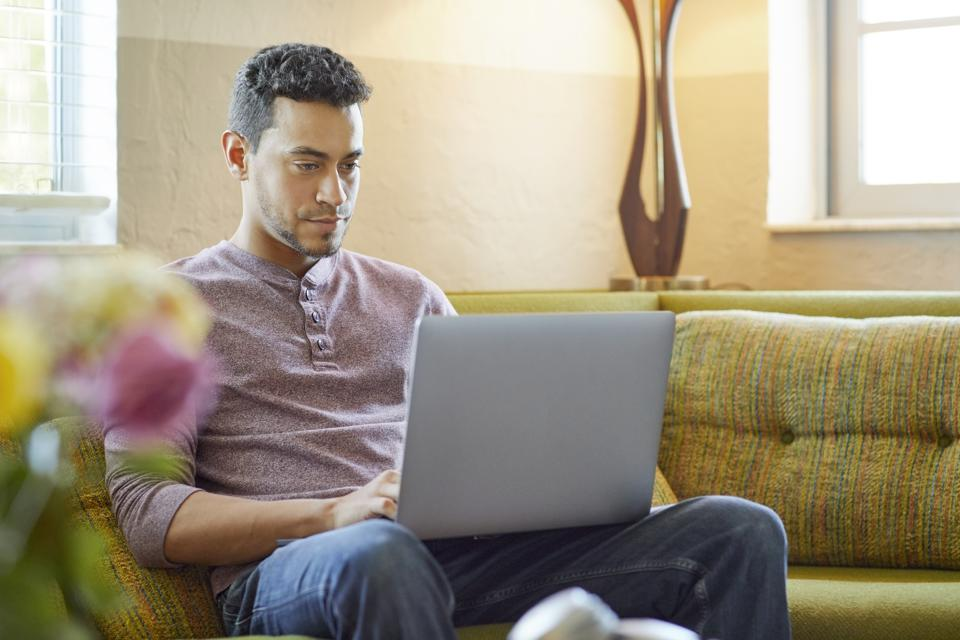 Young man using laptop on couch at home