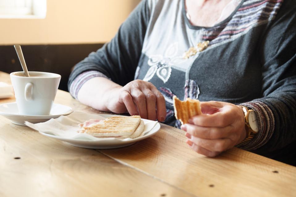 Senior woman eating a sandwich
