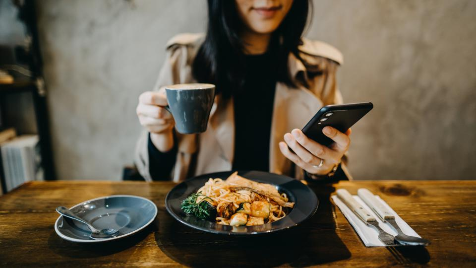 A model checks her smartphone while in a restaurant.