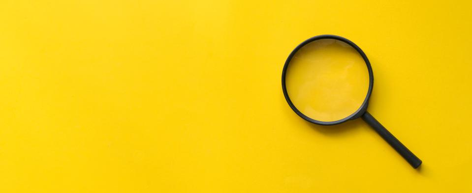 A close up image of a magnifying glass on yellow background