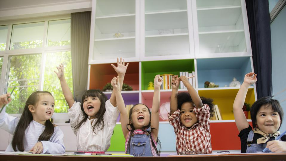 Small children sit in a classroom.