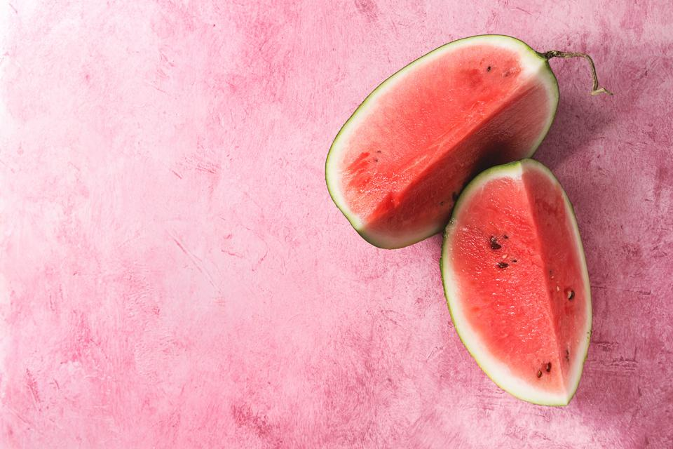 Ripe sliced watermelon over pink texture background Flat lay, space
