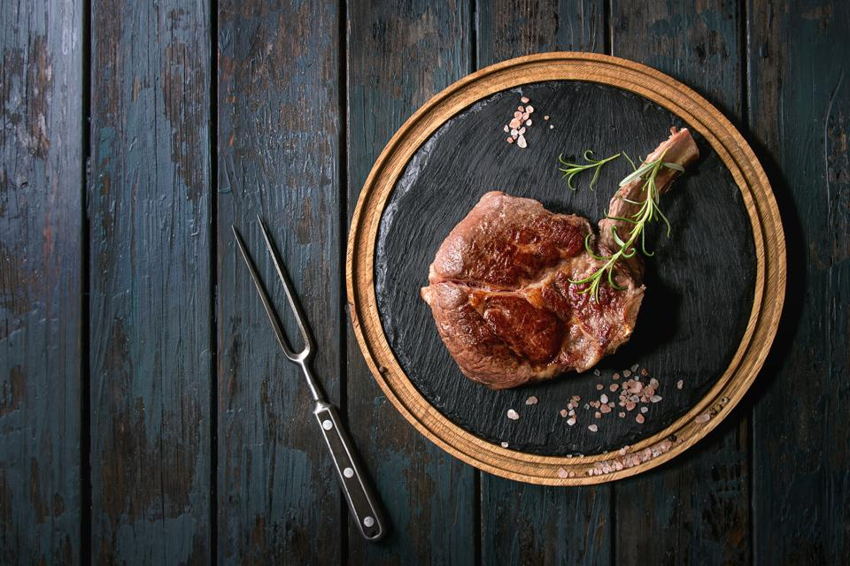 Grilled black angus beef tomahawk steak on bone served with salt, pepper and rosemary on round wooden slate cutting board with meat fork over dark wooden plank background Top view, copy space