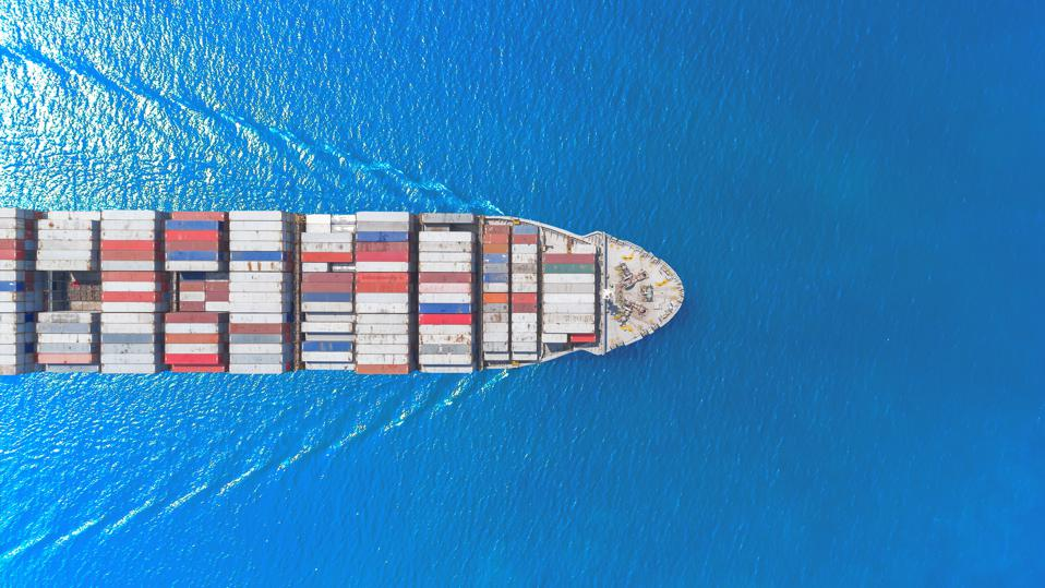 Aerial top view container ship full load container wih beautiful wave pattern for logistics import export, shipping or transportation concept.